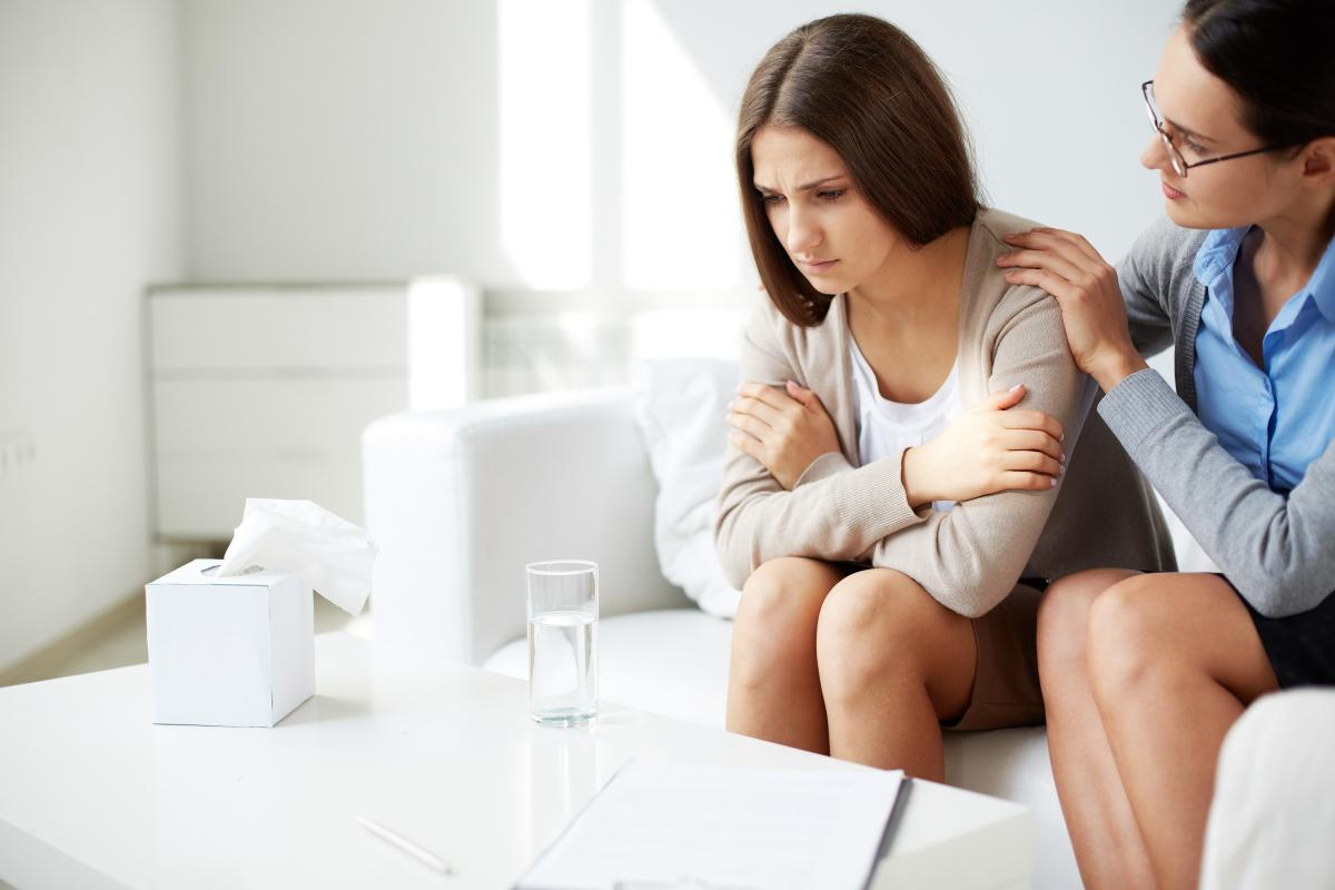 woman comforting another woman