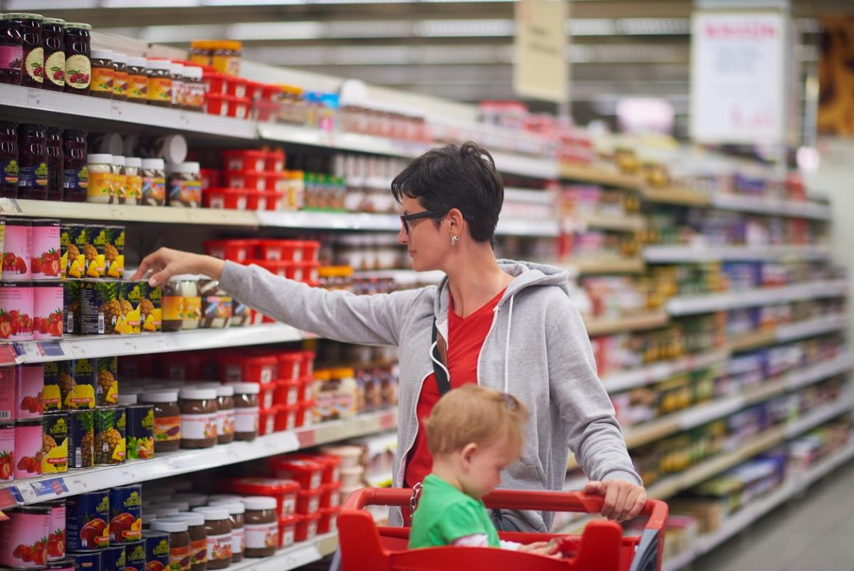 woman grocery shopping with child in cart