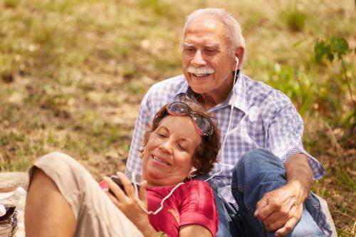 two older adults sitting on the grass, smiling