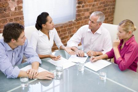 group of diverse people sitting around a table, talking