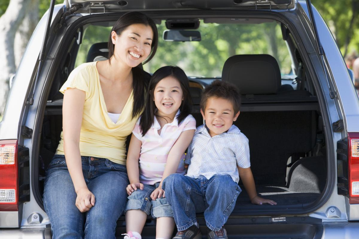 woman with two children, sitting at the back of a van